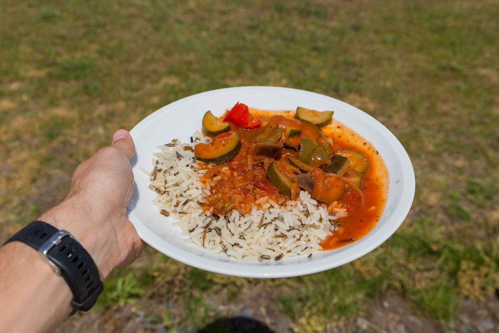 Hand shows vegan ratatouille made from zucchini, tomato and onions at the BarCamp Koblenz in the Center For Nutrition And Health
