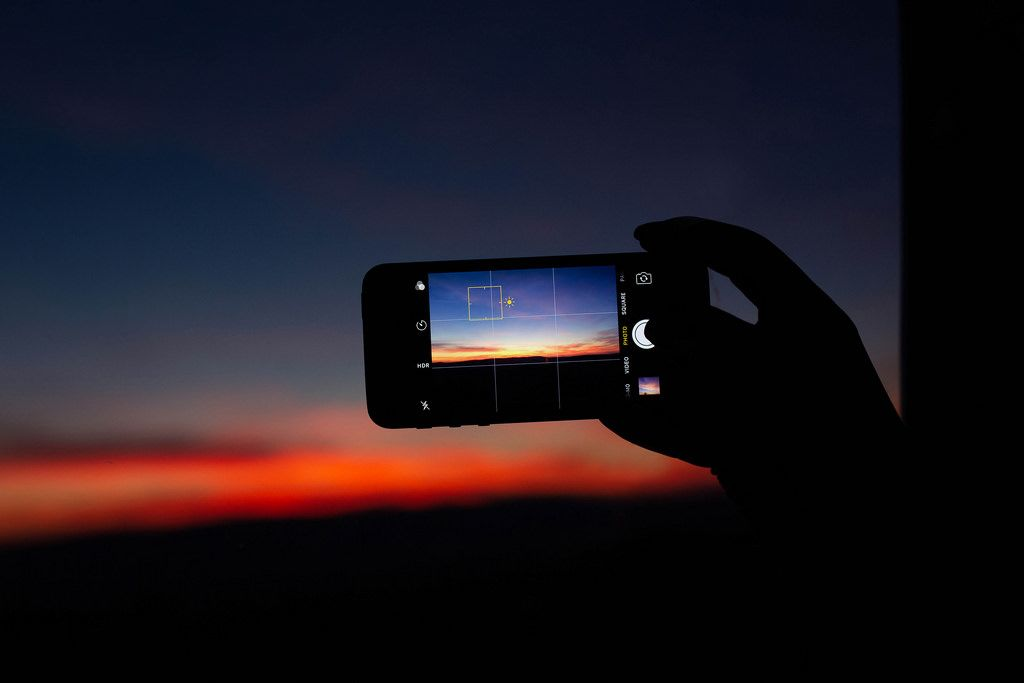 Hand taking photo of a pink sunset with a phone
