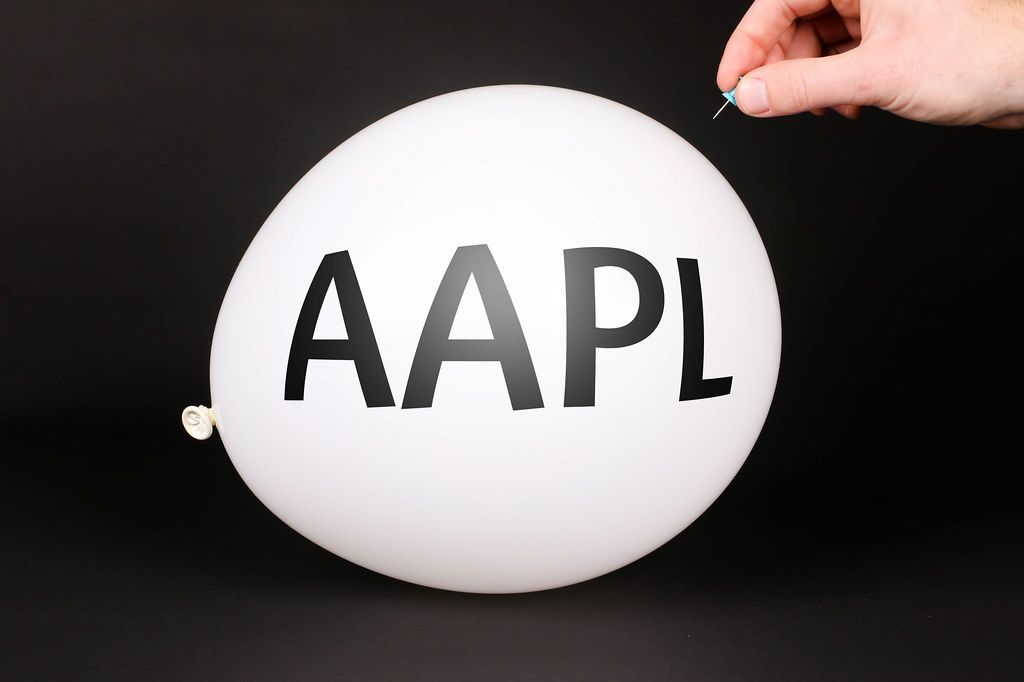 Hand uses a needle to burst a balloon with AAPL text