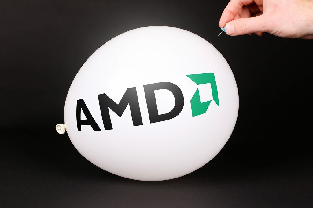 Hand uses a needle to burst a balloon with AMD logo