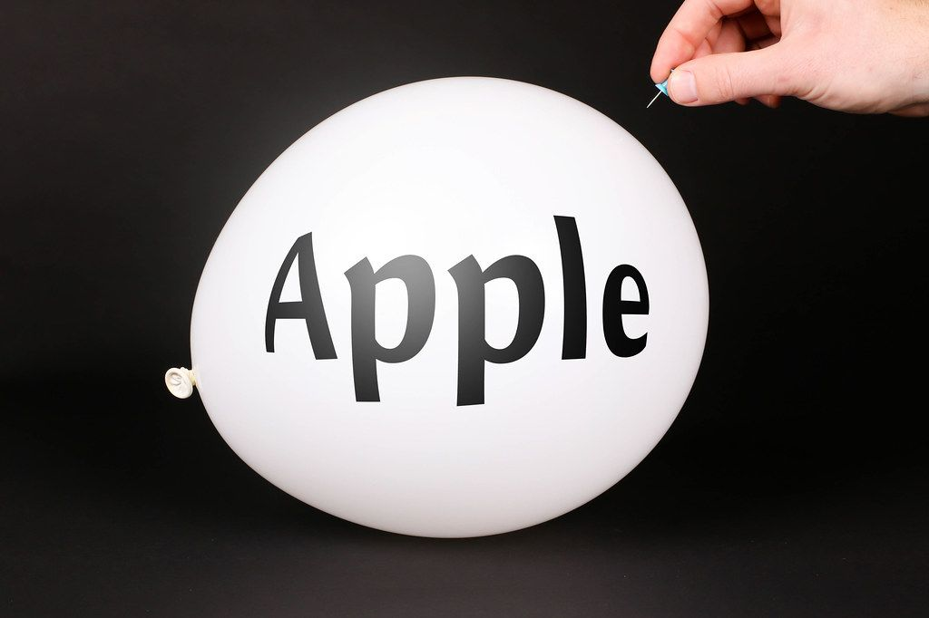 Hand uses a needle to burst a balloon with Apple text