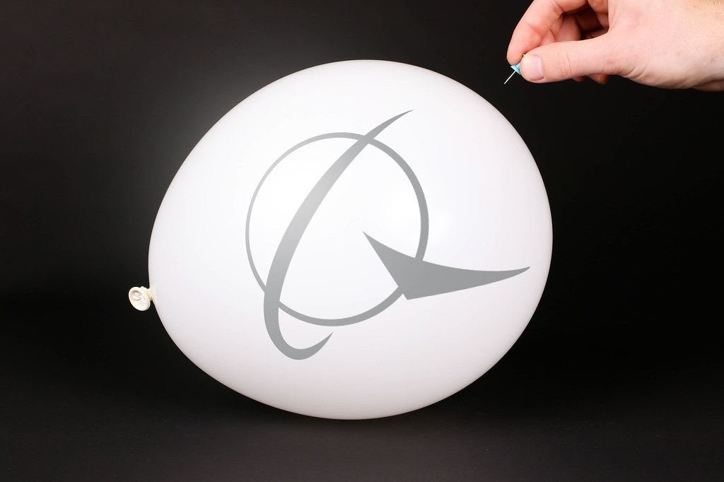 Hand uses a needle to burst a balloon with Boeing icon