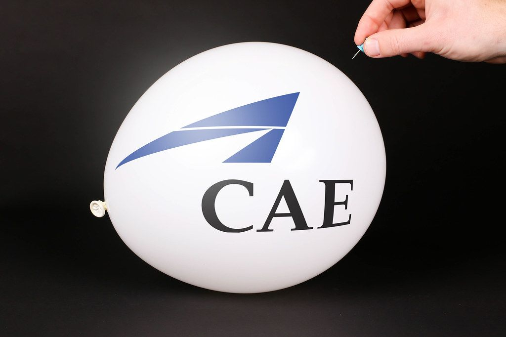 Hand uses a needle to burst a balloon with CAE logo