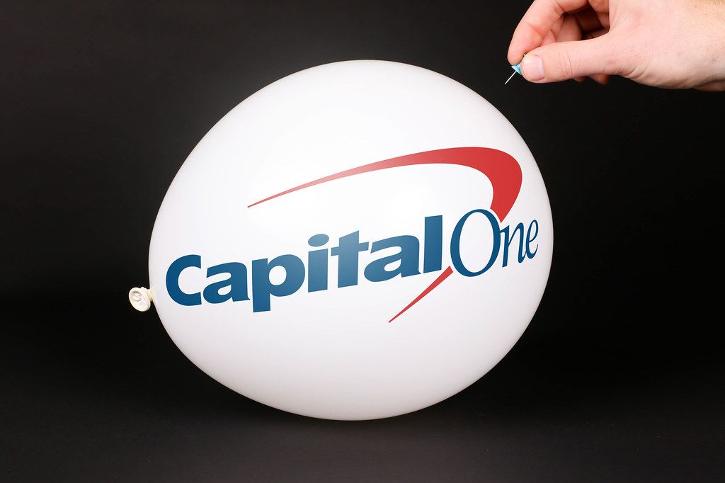 Hand uses a needle to burst a balloon with Capital One logo