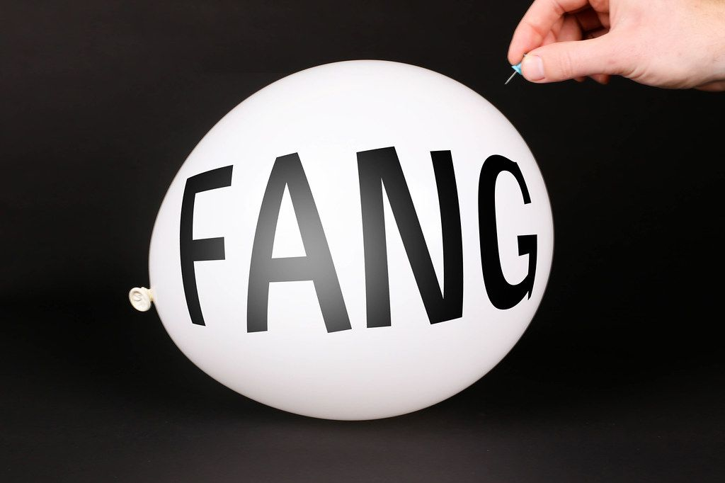 Hand uses a needle to burst a balloon with FANG text