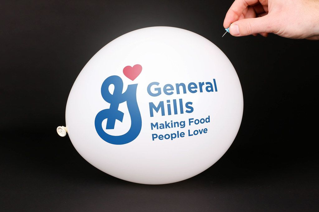 Hand uses a needle to burst a balloon with General Mills logo