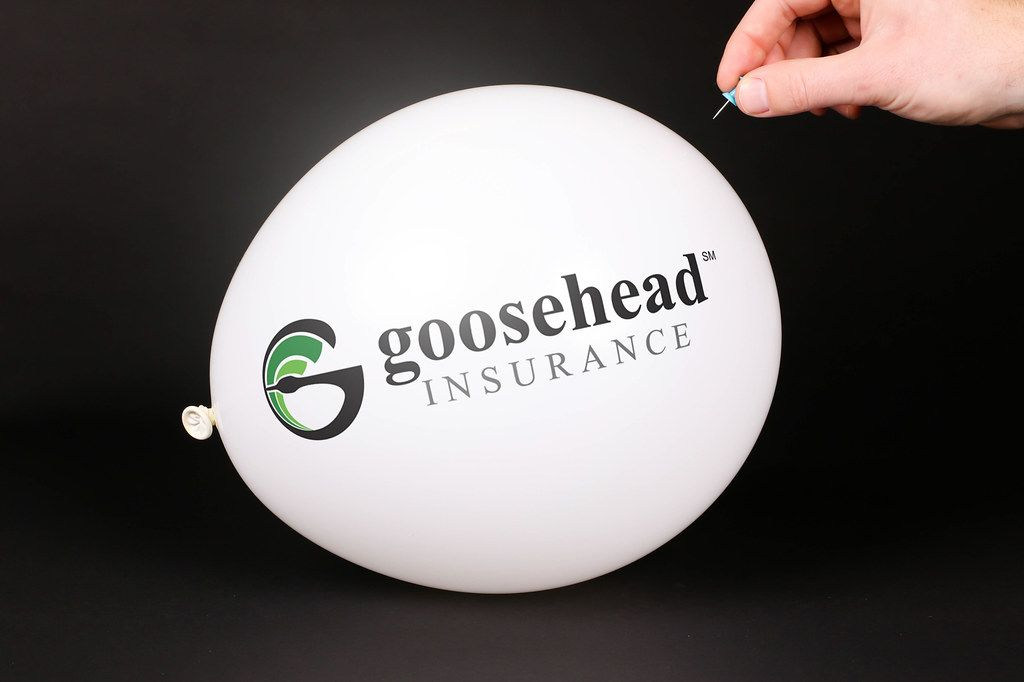 Hand uses a needle to burst a balloon with Gosehead Insurance logo