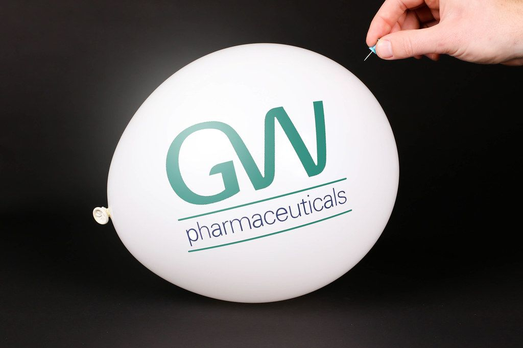 Hand uses a needle to burst a balloon with GW Pharmaceuticals logo