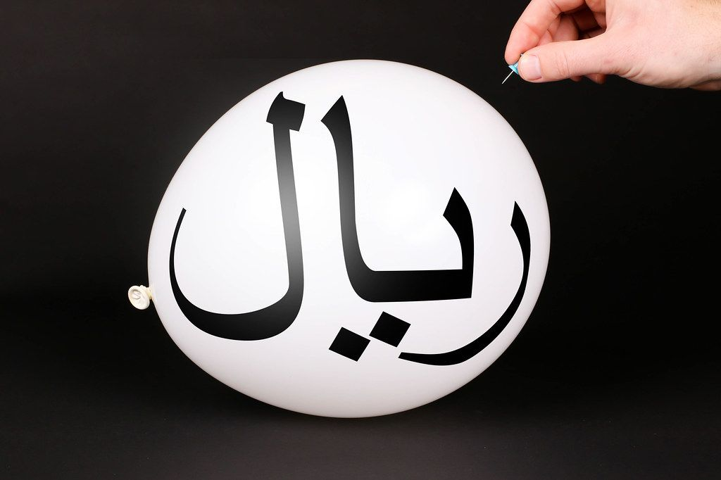 Hand uses a needle to burst a balloon with Iranian Rial symbol