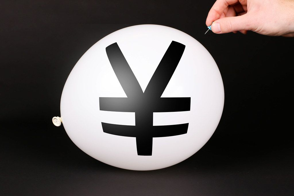 Hand uses a needle to burst a balloon with Japanese Yen symbol