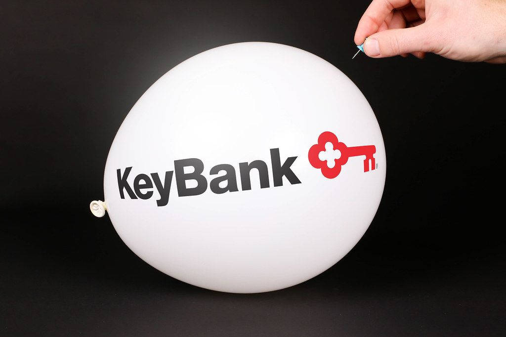 Hand uses a needle to burst a balloon with KeyBank logo