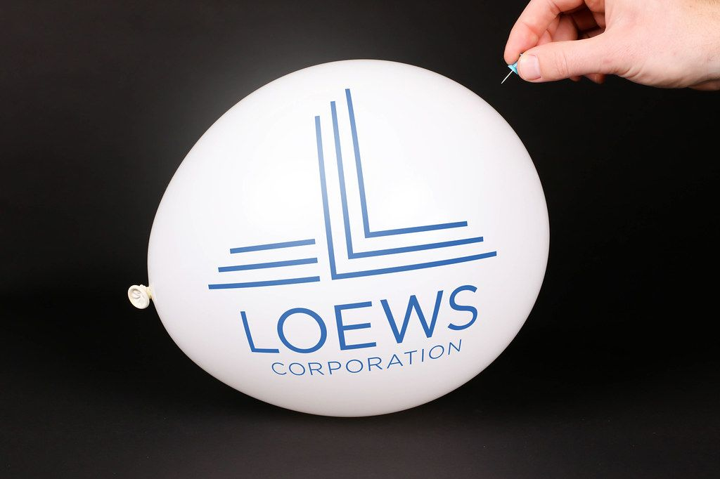 Hand uses a needle to burst a balloon with Loews logo