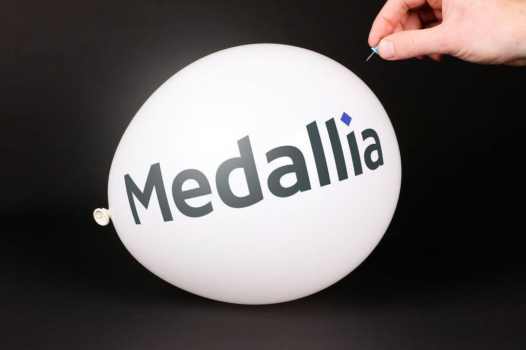 Hand uses a needle to burst a balloon with Medallia logo