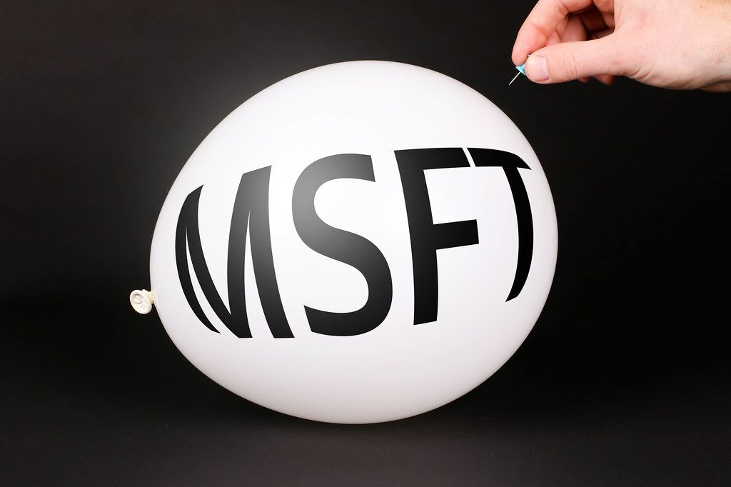 Hand uses a needle to burst a balloon with MSFT text