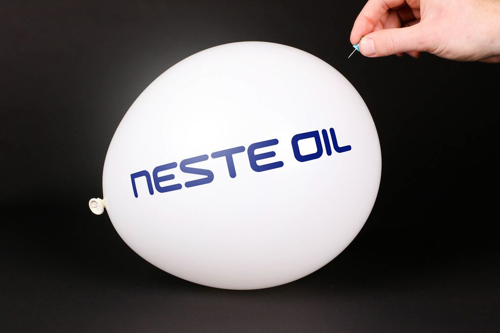 Hand uses a needle to burst a balloon with Neste Oil logo