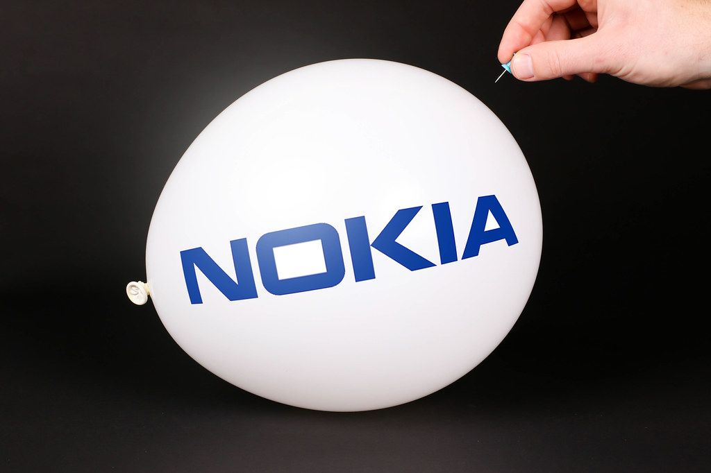 Hand uses a needle to burst a balloon with Nokia logo