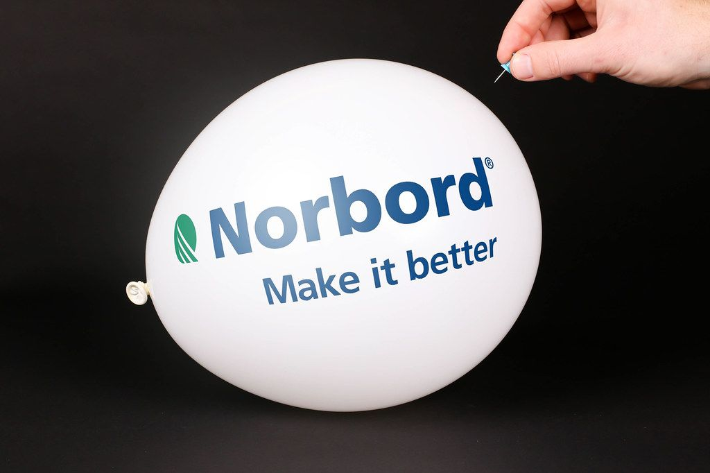 Hand uses a needle to burst a balloon with Norbord logo