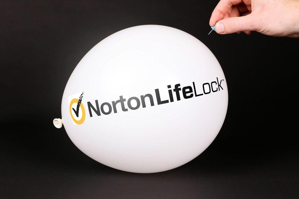 Hand uses a needle to burst a balloon with Norton LifeLock logo