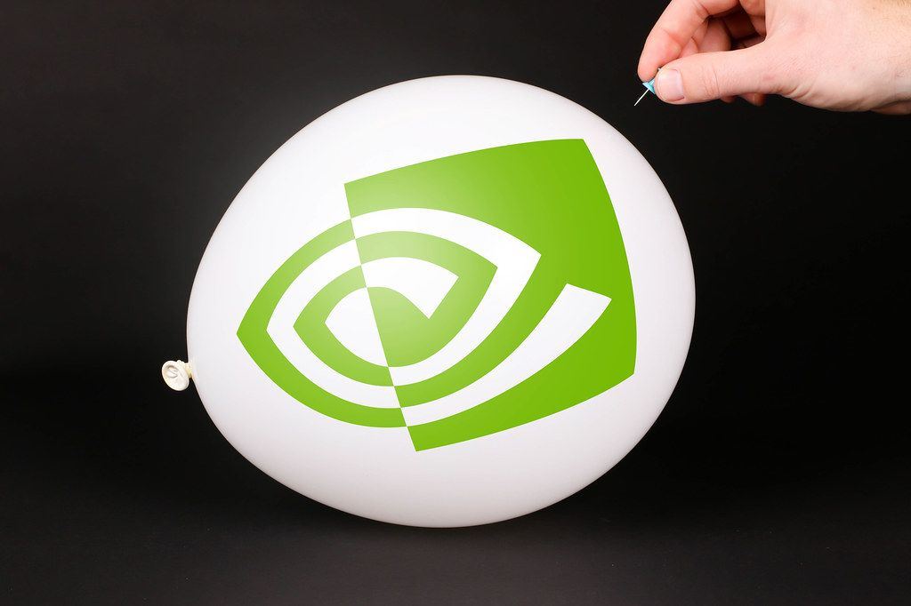 Hand uses a needle to burst a balloon with Nvidia icon