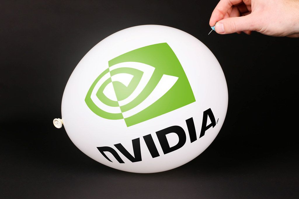 Hand uses a needle to burst a balloon with Nvidia logo