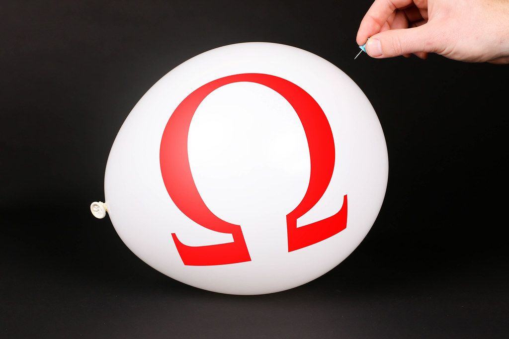Hand uses a needle to burst a balloon with Omega logo