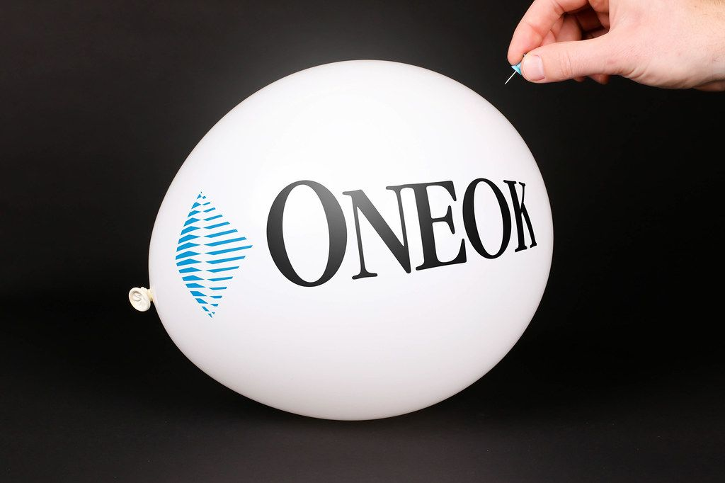 Hand uses a needle to burst a balloon with Oneok logo