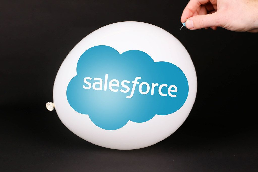 Hand uses a needle to burst a balloon with Salesforce logo
