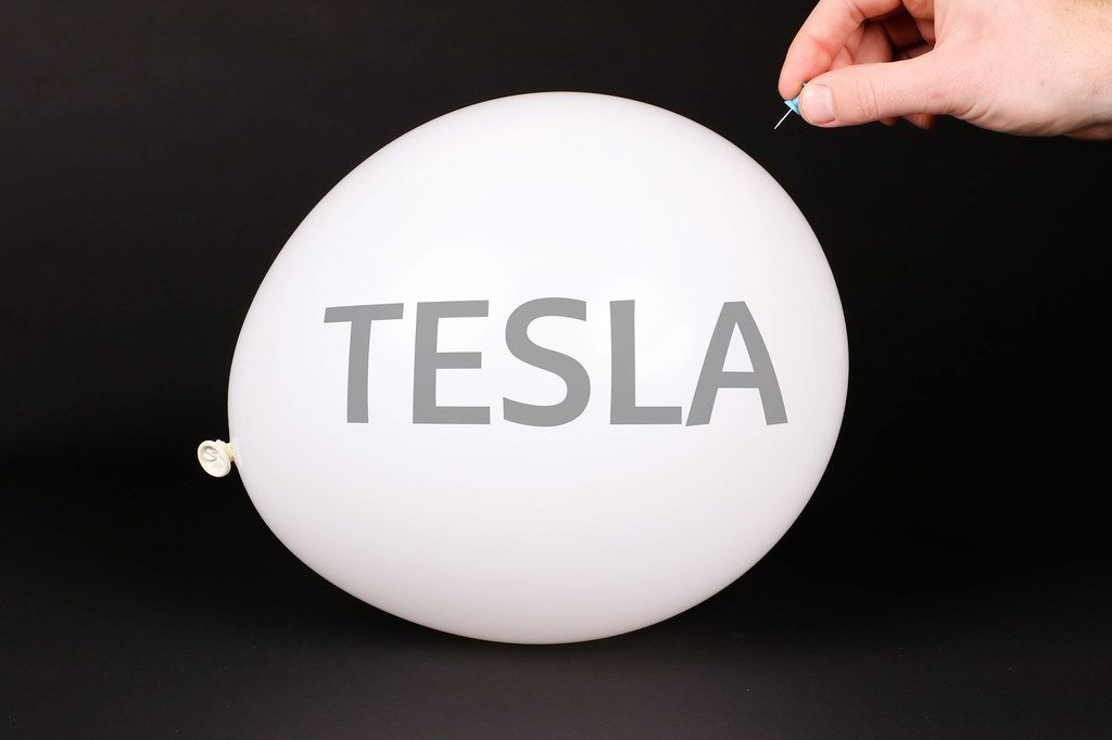 Hand uses a needle to burst a balloon with TESLA text
