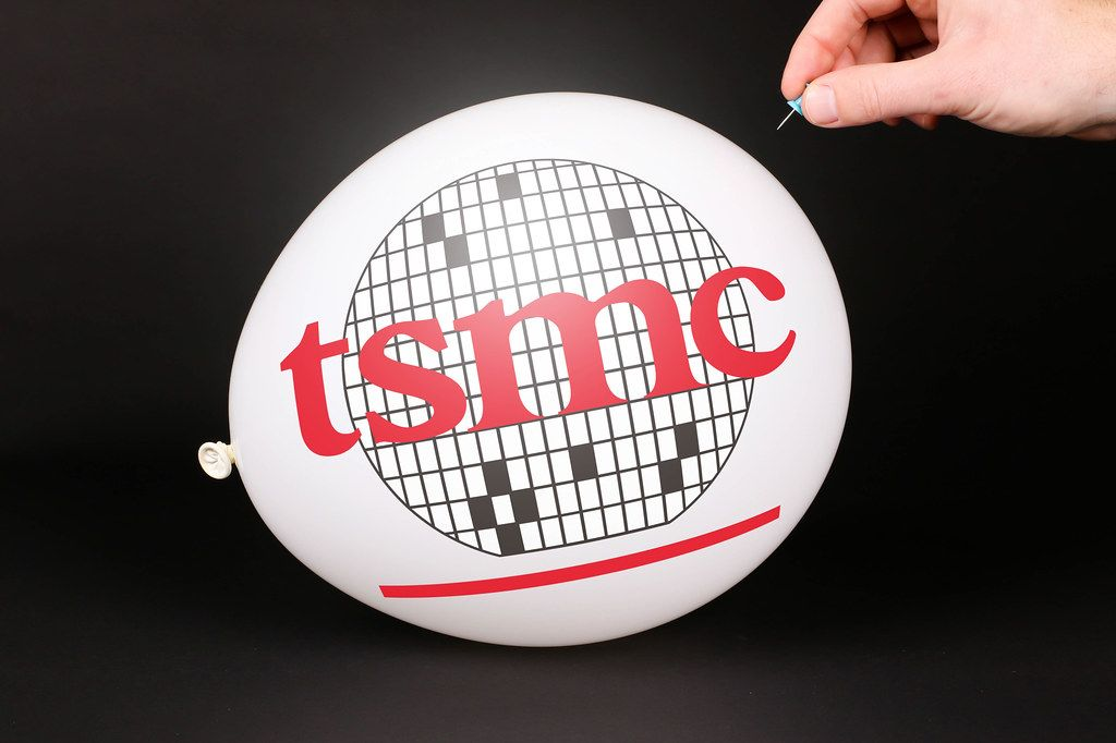 Hand uses a needle to burst a balloon with TSMC logo