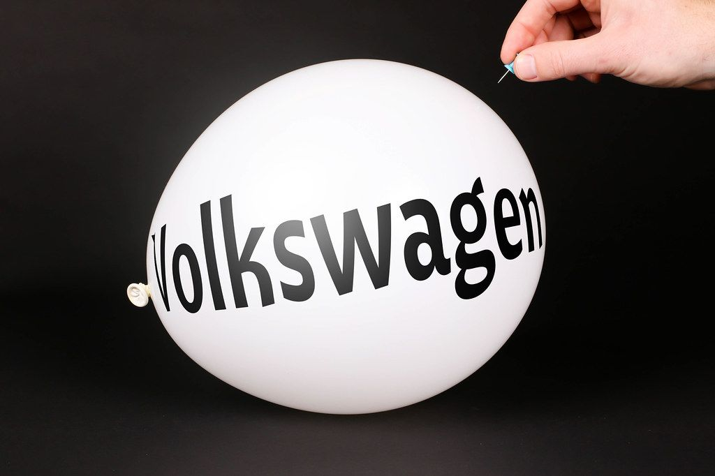Hand uses a needle to burst a balloon with Volkswagen text