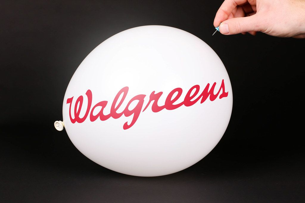 Hand uses a needle to burst a balloon with Walgreens logo