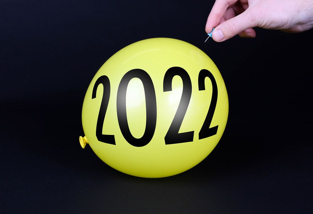 Hand uses a needle to burst a yellow balloon with 2022 text