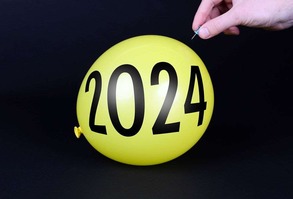 Hand uses a needle to burst a yellow balloon with 2024 text