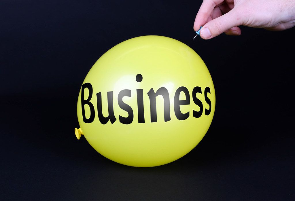 Hand uses a needle to burst a yellow balloon with Business text