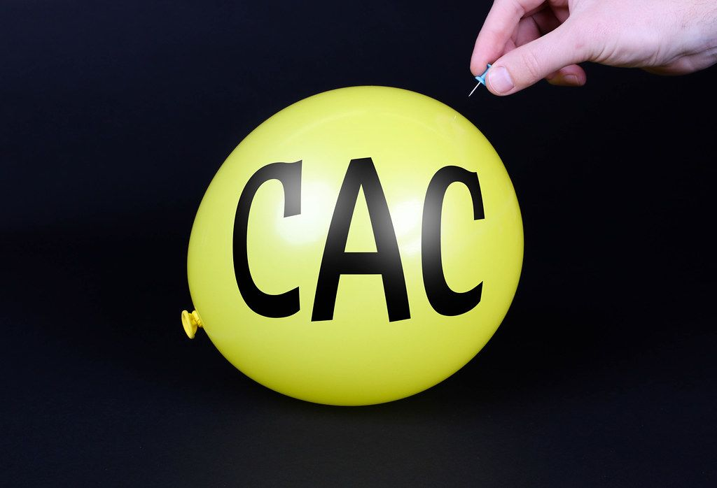 Hand uses a needle to burst a yellow balloon with CAC text