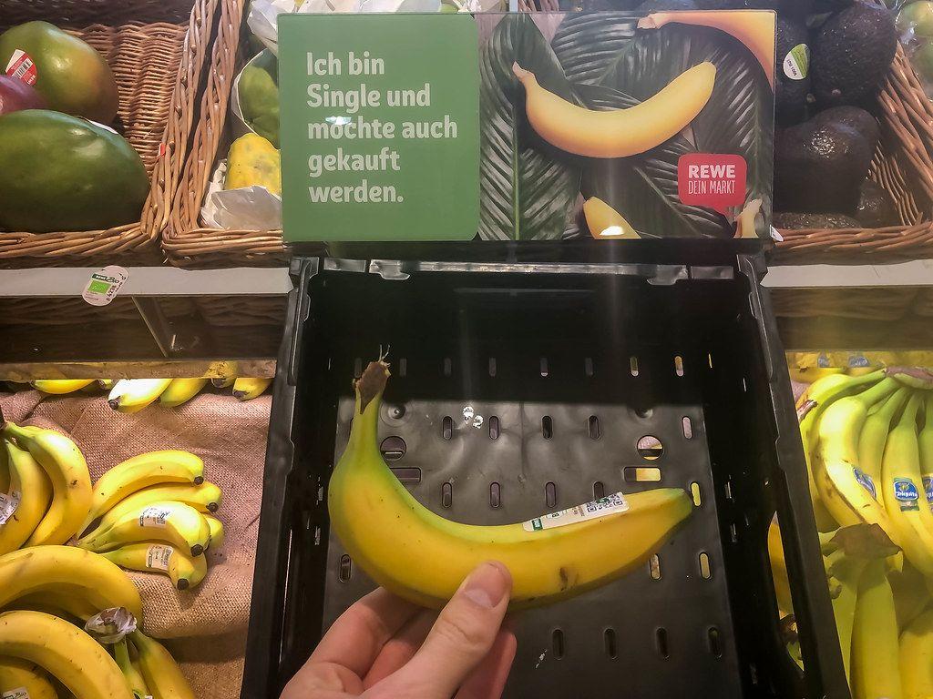 Hand von einem Kunden, der eine einzel verkaufte Banane bei Rewe kauft. Die Kampagne läutet