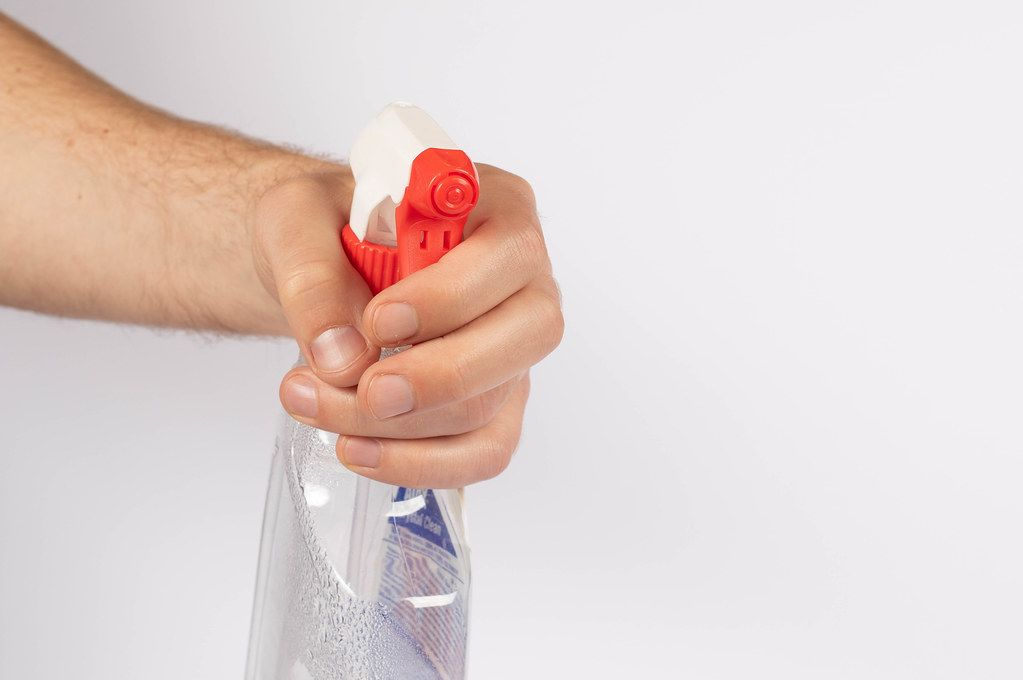 Hand with a cleaning product on white background
