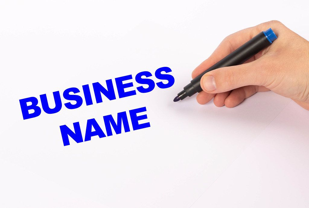 Hand with blue marker writing Business name text
