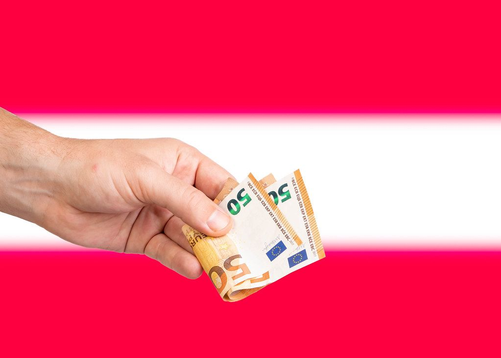 Hand with Euro banknotes over flag of Austria