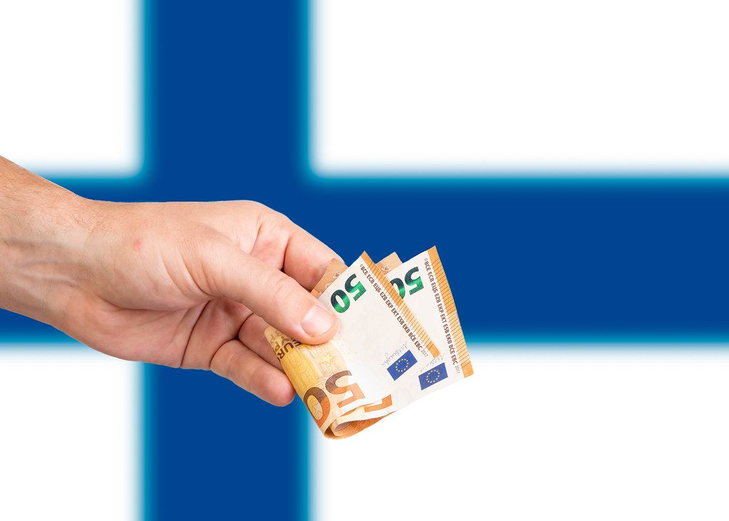 Hand with Euro banknotes over flag of Finland