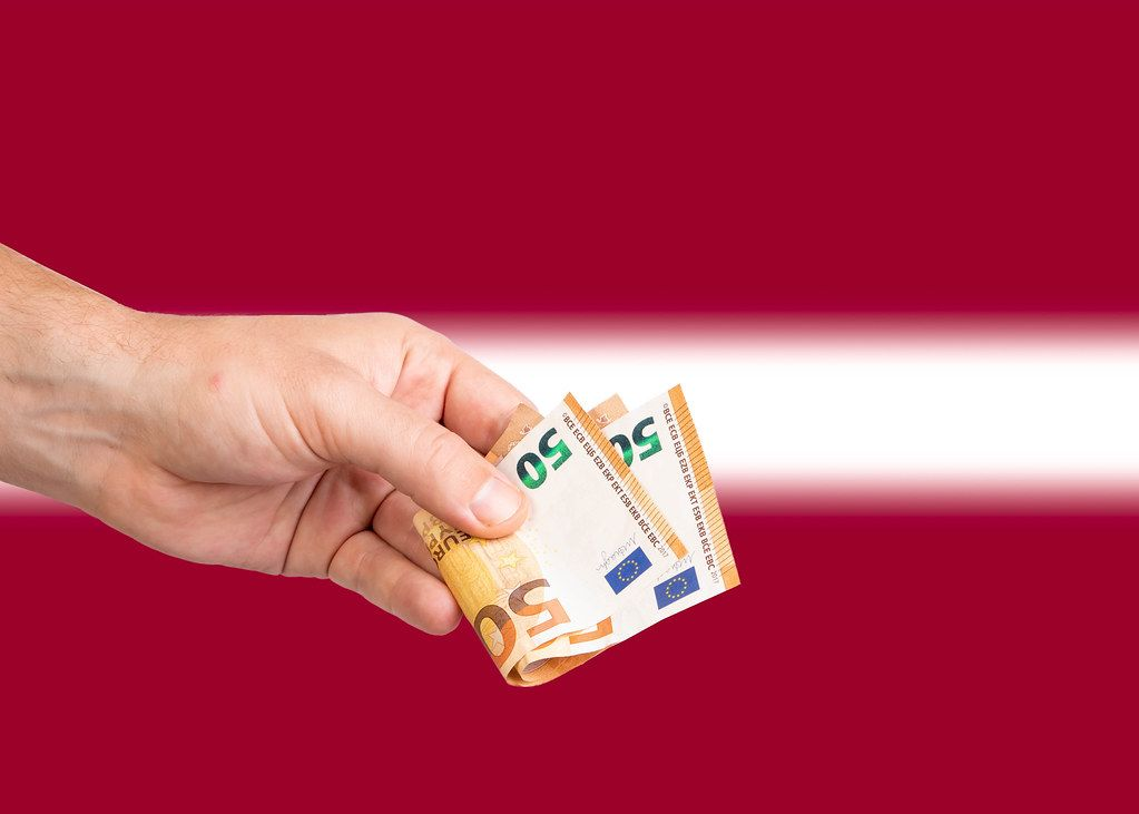 Hand with Euro banknotes over flag of Latvia