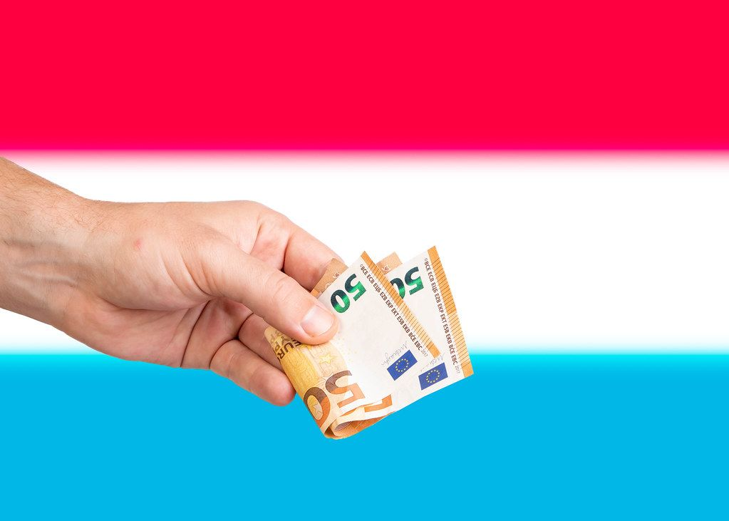 Hand with Euro banknotes over flag of Luxembourg