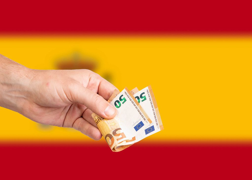 Hand with Euro banknotes over flag of Spain