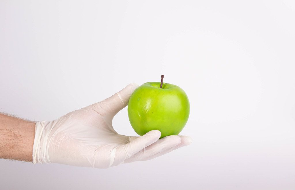Hand with gloves holding green apple