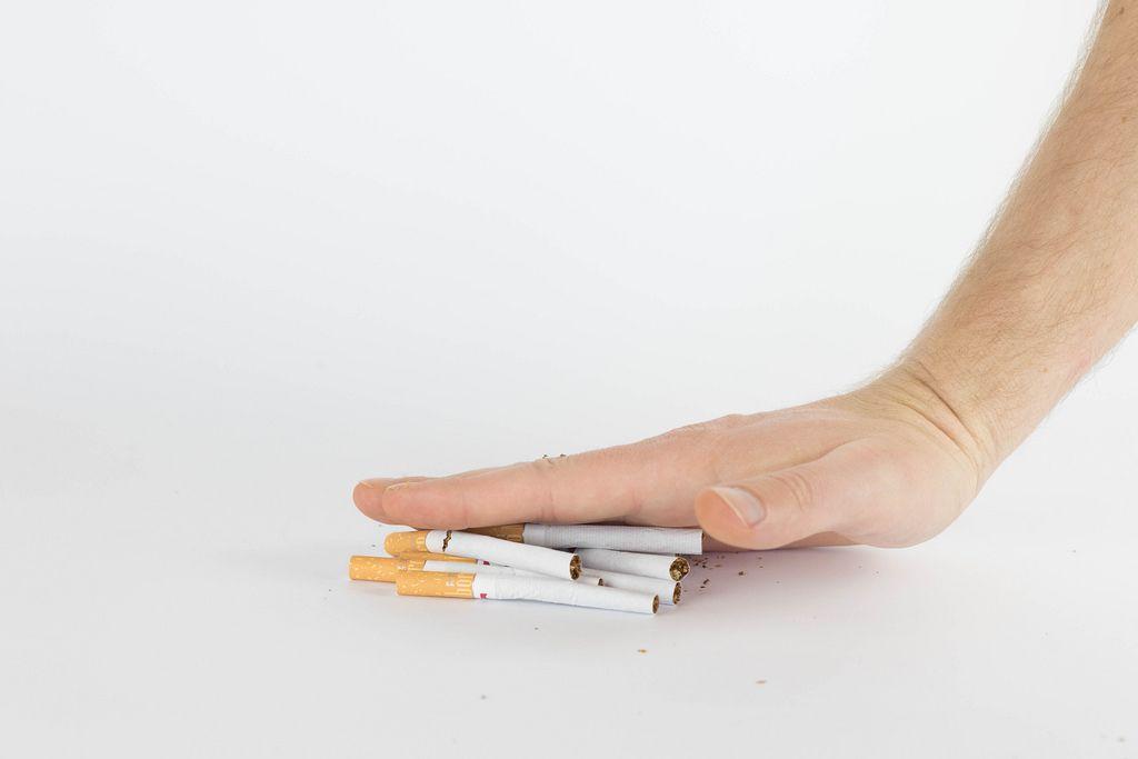 Hand zerschmettert ein Haufen von Zigaretten