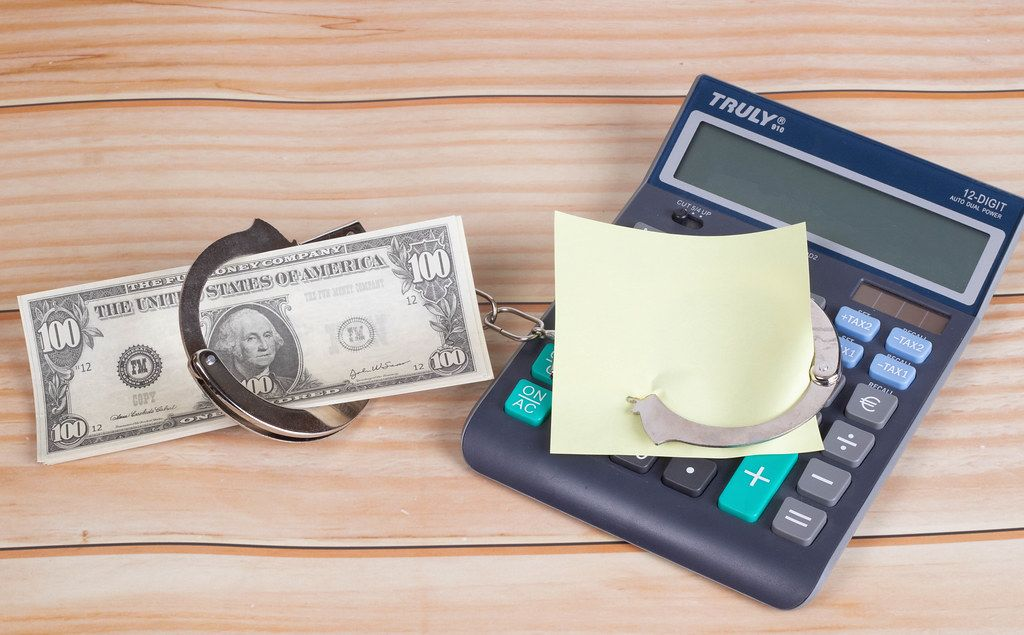 Handcuffs with money, calculator and empty sticky note