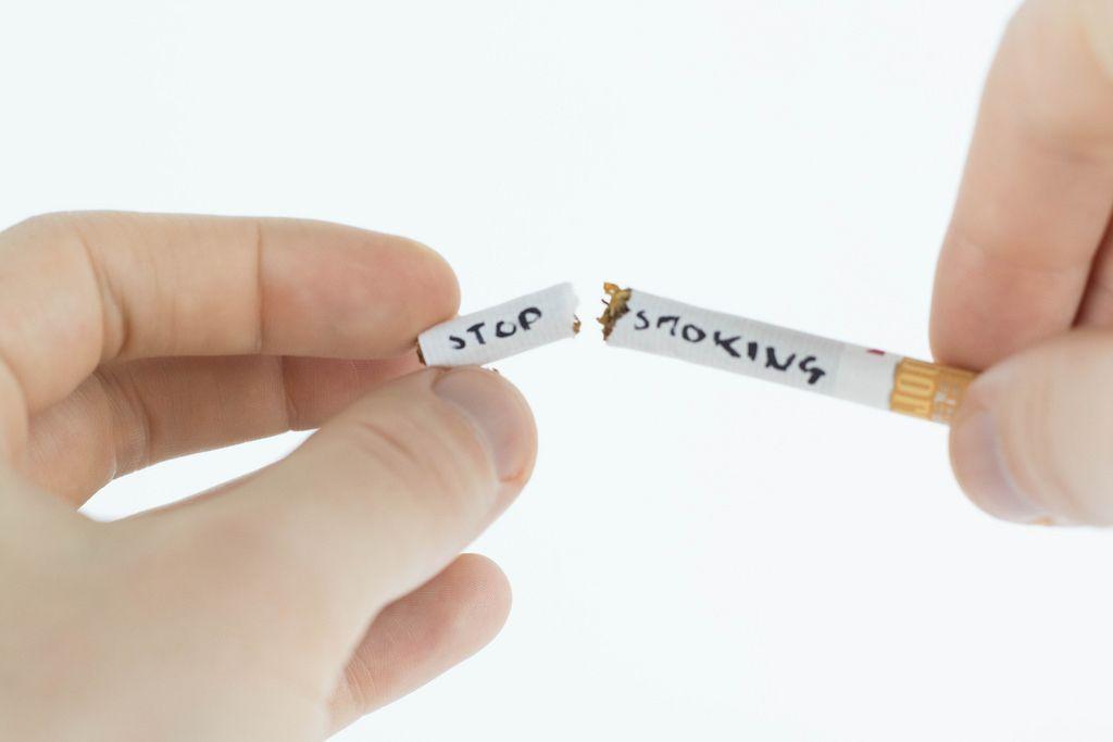 Hände brechen Zigarette in zwei Teile