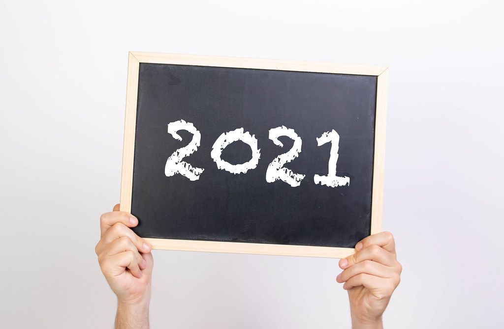Hands holding blackboard with 2021 text
