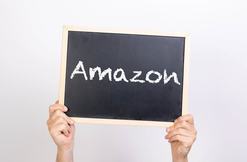 Hands holding blackboard with text Amazon