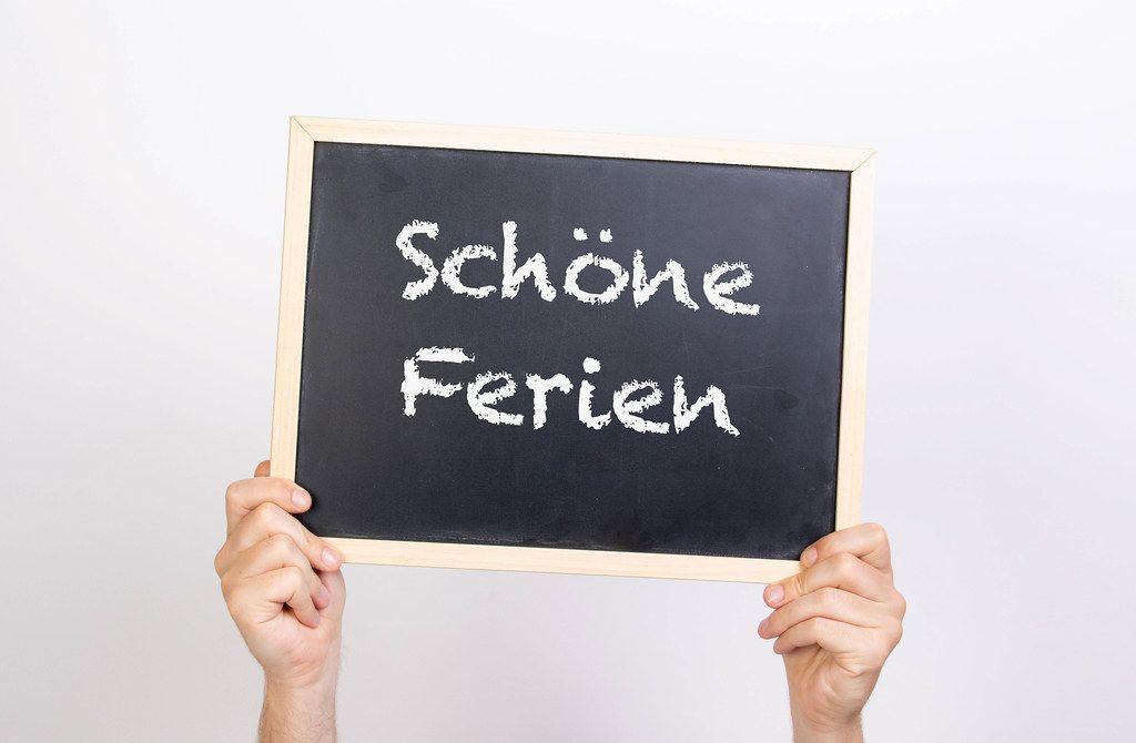 Hands holding blackboard with text Schöne Ferien